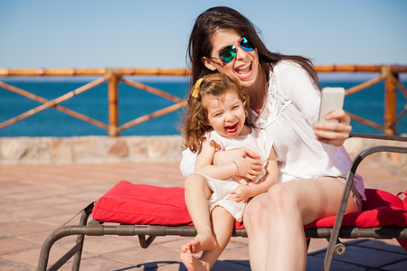 Foto de Little girl and her mom having some fun at the beach and taking a selfie with a smartphone - Imagen libre de derechos