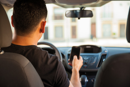 Photo for Rear view of a young man using his smartphone and texting while driving - Royalty Free Image