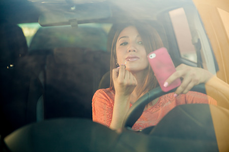 Photo for Portrait of a distracted young woman looking at her smartphone and putting some lipstick on while driving a car - Royalty Free Image