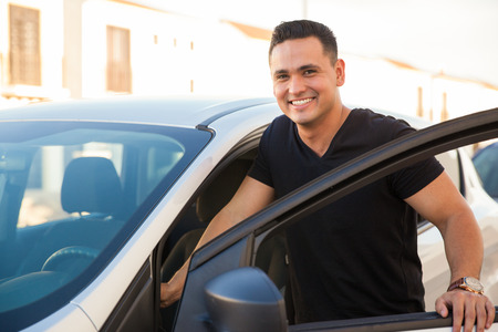 Photo for Portrait of a Hispanic young handsome man getting into his car and smiling - Royalty Free Image