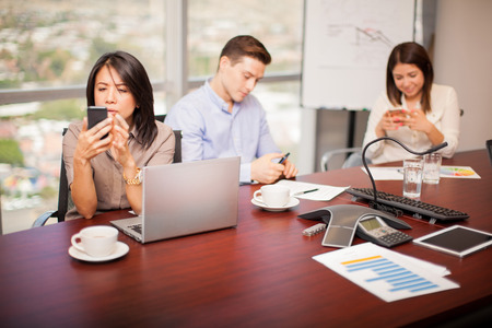 Photo pour Group of people in a meeting room using their smartphones and ignoring work for a while - image libre de droit