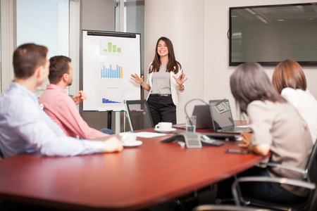 Photo for Beautiful young Latin brunette giving a business presentation to some of her clients in a meeting room - Royalty Free Image