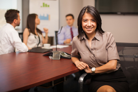 Photo pour Beautiful Hispanic young lawyer sitting in a meeting room with some of her colleagues and smiling - image libre de droit