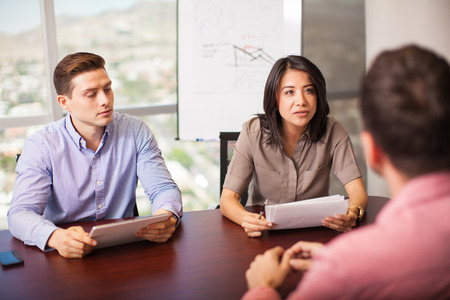 Photo for Couple of Latin people with resume in hand interviewing a job candidate in a meeting room - Royalty Free Image