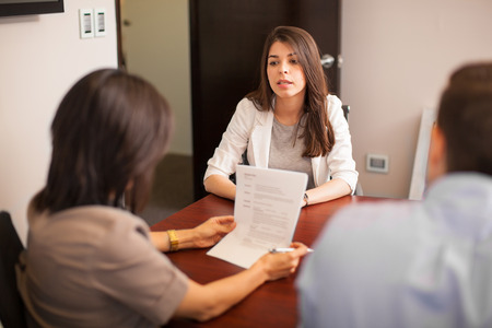 Photo for Portrait of a young Hispanic woman sitting in front of two people during a job interview - Royalty Free Image