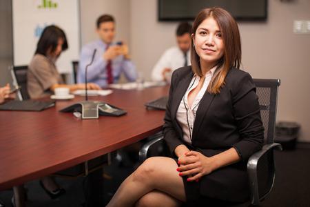 Foto de Young Hispanic businesswoman sitting in a meeting room with some of her colleagues - Imagen libre de derechos