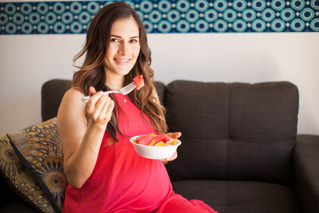 Goodlooking pregnant woman eating healthy food in her living room and smiling
