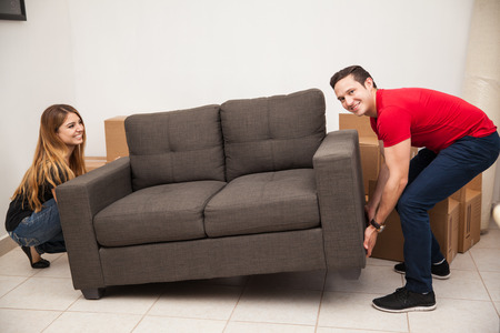 Photo for Young couple of newlyweds trying to move a couch to their new apartment - Royalty Free Image