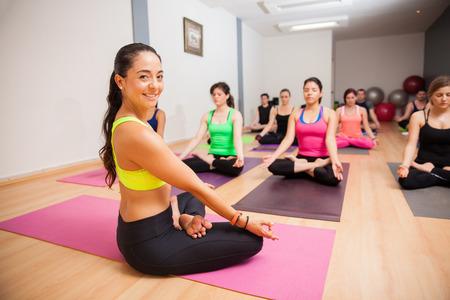 Foto de Portrait of a beautiful young yoga instructor smiling during one of her classes - Imagen libre de derechos