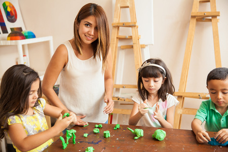 Foto de Portrait of a beautiful Latin teacher and her students working with clay during sculpting class - Imagen libre de derechos