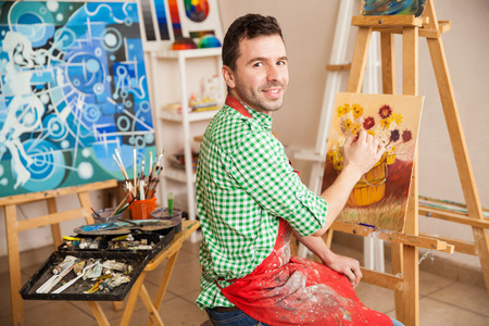 Photo for Portrait of a young attractive man working on a painting of flowers and enjoying his work as an artist - Royalty Free Image