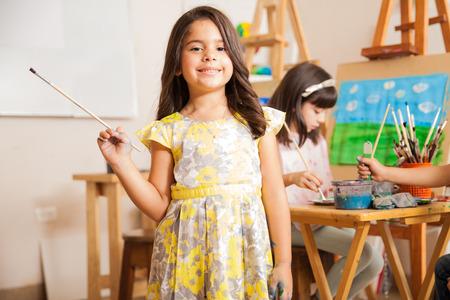 Foto de Cute Hispanic little girl smiling in front of her classroom during art class - Imagen libre de derechos