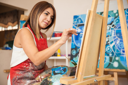 Photo for Focused young female artist working on a new painting in her workshop - Royalty Free Image