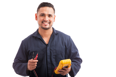 Photo pour Portrait of a young Hispanic electrician wearing overalls using a multimeter and smiling on a white background - image libre de droit