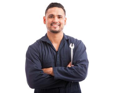 Foto de Portrait of a young mechanic holding a wrench and smiling, ready to fix cars - Imagen libre de derechos
