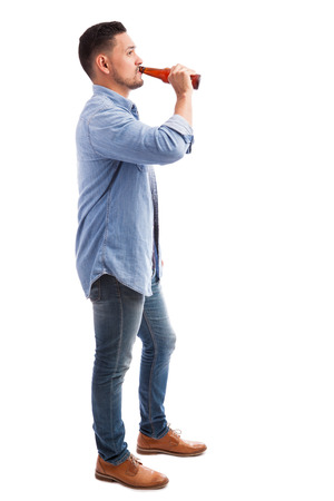 Foto de Full length profile view of a young Hispanic man drinking beer from a bottle against a white background - Imagen libre de derechos