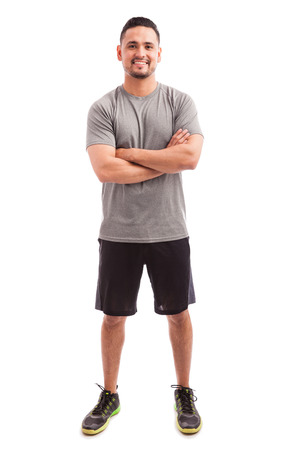 Foto de Male Hispanic fitness coach with his arms crossed and smiling on a white background - Imagen libre de derechos