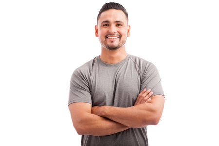 Foto de Handsome Latin athlete in a sporty outfit with his arms crossed and smiling on a white background - Imagen libre de derechos
