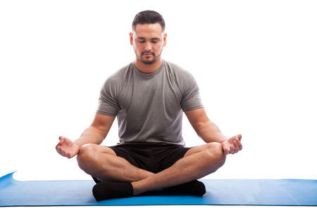Photo for Portrait of a young man sitting on a yoga mat and doing some meditation with his eyes closed - Royalty Free Image