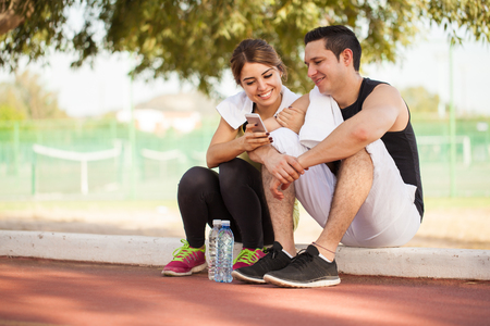Photo pour Portrait of a young couple taking a break from exercising together and looking at some pictures on a smartphone - image libre de droit