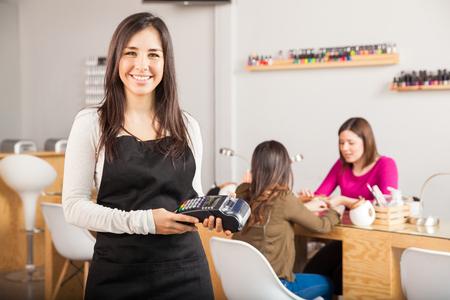 Photo pour Portrait of a cute young Latin woman holding a credit card terminal at a nail salon and smiling - image libre de droit