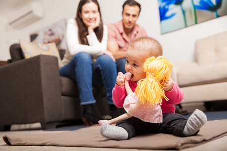 Couple of young parents watching their baby girl play with a doll at home