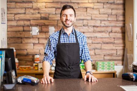 Foto de Portrait of a handsome young Hispanic business owner standing at the checkout counter and smiling - Imagen libre de derechos