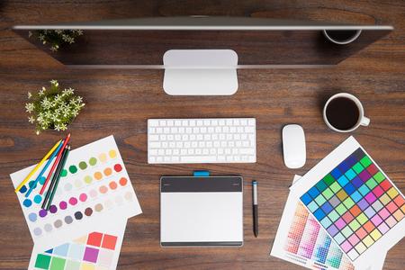Foto de Top view of a wooden desk with a computer some coffee, a pen tablet and a few color swatches in a graphic designer's workspace - Imagen libre de derechos