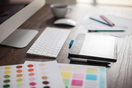 Foto de Shallow depth of field closeup of a graphic designer's workspace with a pen tablet, a computer and some color swatches - Imagen libre de derechos
