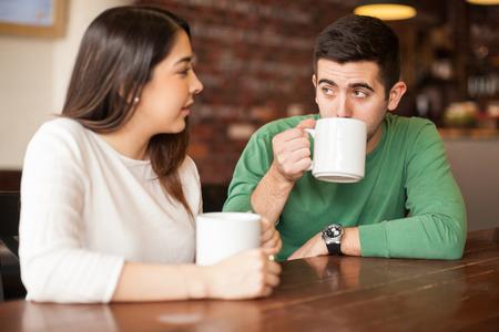 Foto de Good looking young couple talking and drinking coffee in a restaurant - Imagen libre de derechos