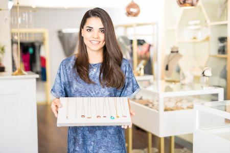 Foto de Pretty young brunette working at a jewelry shop and showing some necklaces with a smile - Imagen libre de derechos