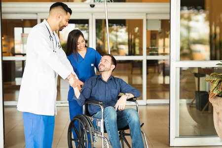 Foto de Happy and recovered patient sitting on a wheelchair and saying goodbye to his doctor while leaving the hospital - Imagen libre de derechos