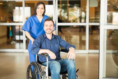 Foto de Portrait of a young Hispanic patient leaving the hospital in a wheelchair after a full recovery - Imagen libre de derechos