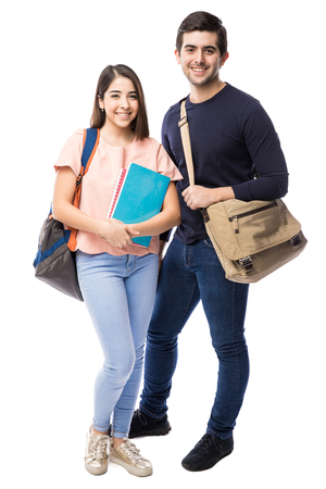 Foto de Attractive young couple of college students with books and school bags in a white background - Imagen libre de derechos