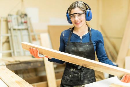 Foto de Cute young female carpenter cutting some wood in a table saw and enjoying her work - Imagen libre de derechos