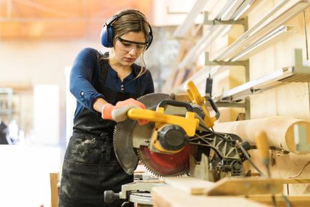 Foto de Attractive female carpenter using some power tools for her work in a woodshop - Imagen libre de derechos