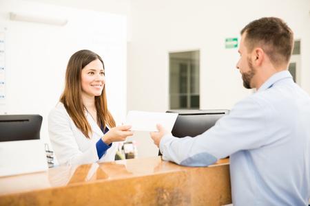 Foto de Attractive receptionist giving an envelope with his test results to a patient in a laboratory - Imagen libre de derechos