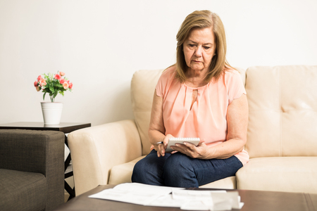 Foto de Beautiful Hispanic elder lady checking her personal finances from bills and savings at home - Imagen libre de derechos