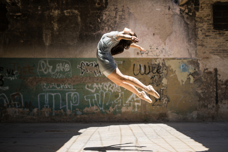Photo for Dramatic portrait of a pretty female ballet dancer jumping and performing outdoors in an urban setting - Royalty Free Image