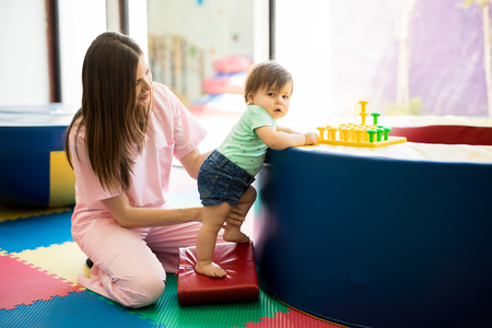 Foto de Portrait of a Hispanic baby standing and practicing maintaining balance while playing in a children therapy center - Imagen libre de derechos
