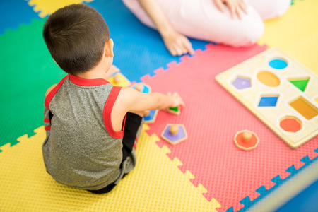 Foto de Top view of a young boy playing and learning different shapes in a therapy and education center - Imagen libre de derechos