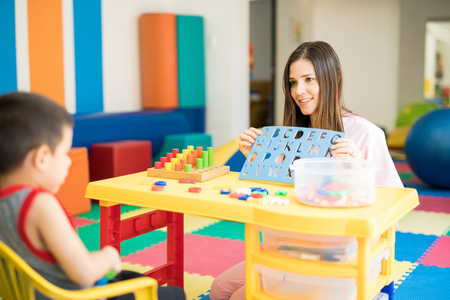 Photo for Portrait of a beautiful female language therapist working and practicing the alphabet with a kid - Royalty Free Image