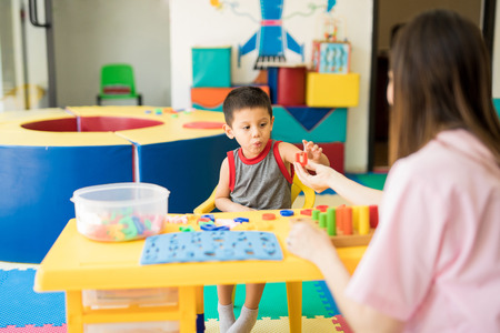 Foto de Toddler learning the alphabet with a language therapist in a special education class - Imagen libre de derechos