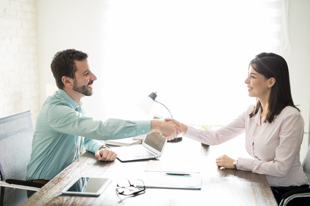 Photo for Attractive business man closing a deal with a woman by shaking hands and signing a contract - Royalty Free Image