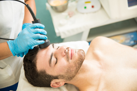 Foto de Relaxed Hispanic young man getting cellular and rejuvenation facial therapy in a spa - Imagen libre de derechos