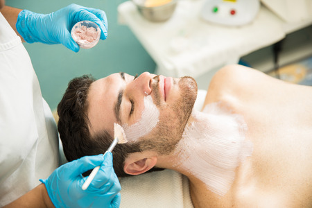 Foto de Handsome young man getting a facial treatment and an anti-aging mask in a health spa - Imagen libre de derechos
