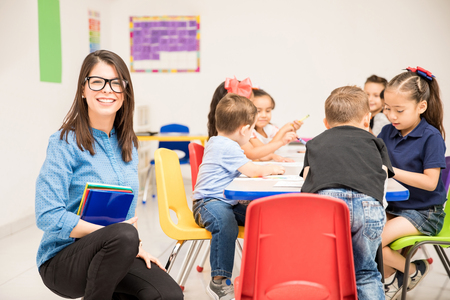 Foto de Good looking brunette teaching kindergarten to a group of students and looking happy - Imagen libre de derechos