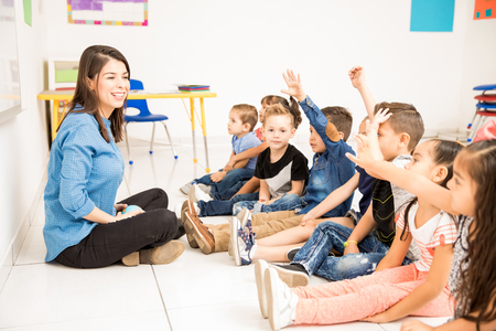 Foto de Beautiful preschool teacher and her group of students raising their hands and having some fun at school - Imagen libre de derechos
