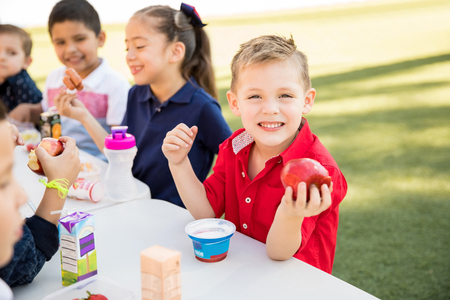 Photo for Handsome Caucasian preschooler enjoying his lunch with some of his friends at school and smiling - Royalty Free Image