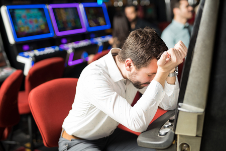 Foto de Unlucky young man feeling sad and stressed after losing his money playing slots in a casino - Imagen libre de derechos